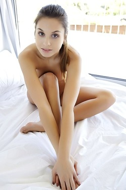 The hot brunette sits on a bed with her legs open